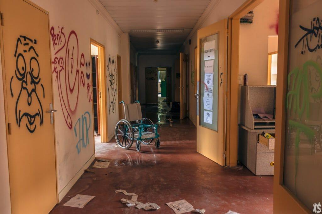 couloir rempli de graffitis et avec au centre une veille chaise roulante  urbex en ile de france