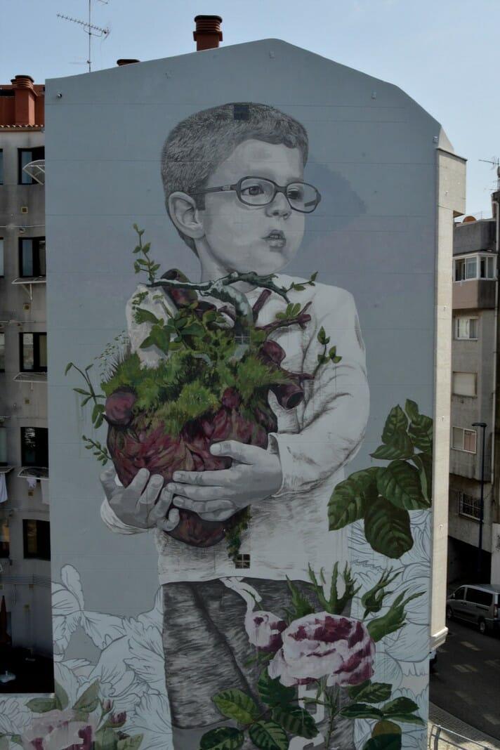 un enfant portant le cœur de la nature, street art