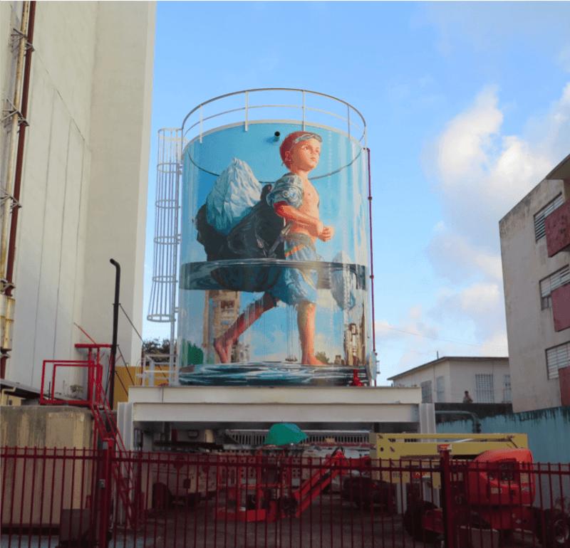 Peinture sur une citerne par Fintan Magee illustrant un petit garçon portant dans son sac un iceberg : Le verre moitié plein