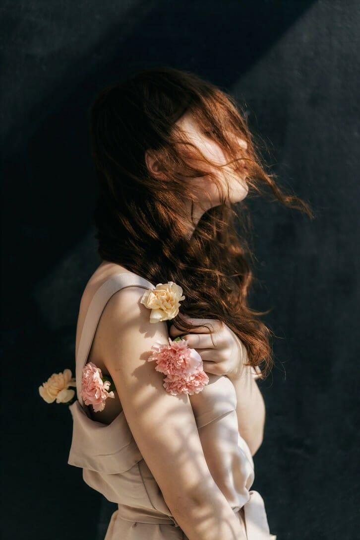 Photographie réalisée par Polina Washington illustrant une jeune femme avec des fleurs