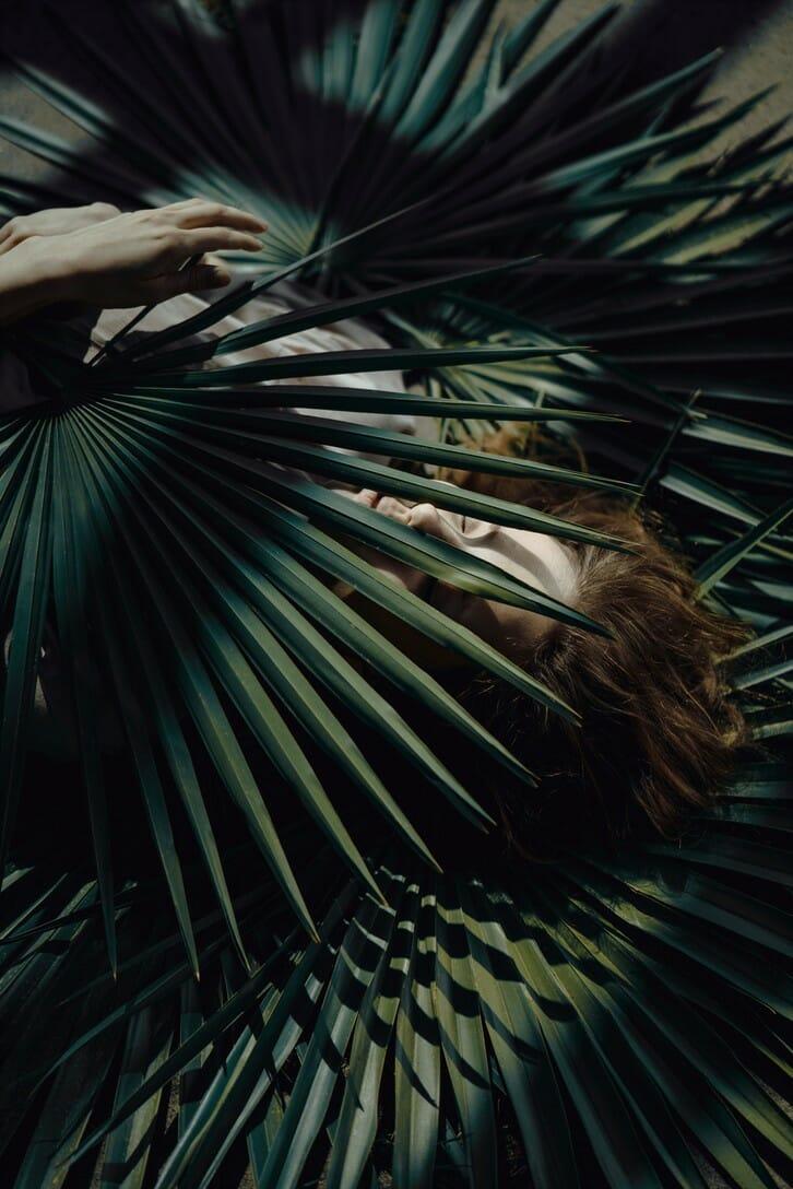 Photographie réalisée par Polina Washington illustrant une femme et des feuilles