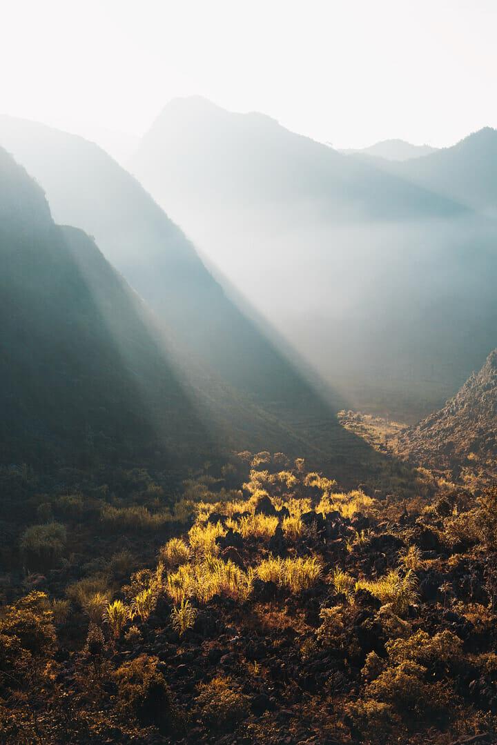 Voici une des impressionnantes photographies de Lukas Furlan :  Vu sur le sol d'une montagne éclairé par des faisceaux de lumière du soleil et encadré d'autres montagnes.