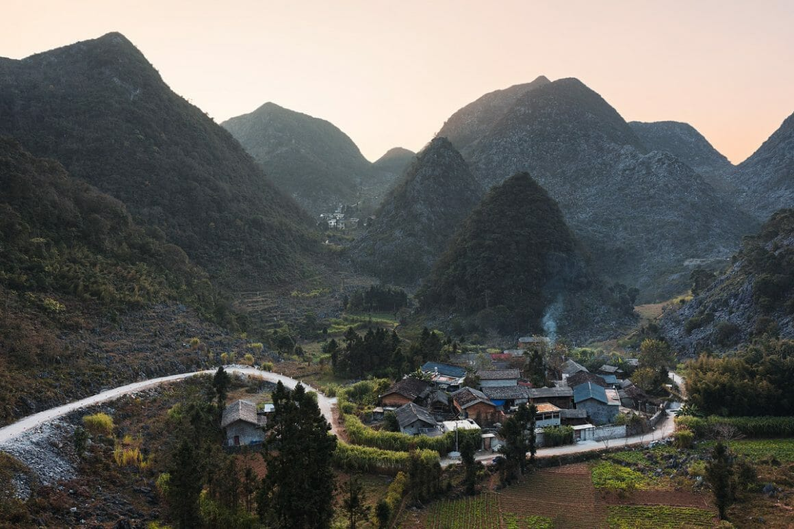 Voici une des impressionnantes photographies de Lukas Furlan : Vue de haut sur un petit village encadré de montagnes. Le ciel est rosé.