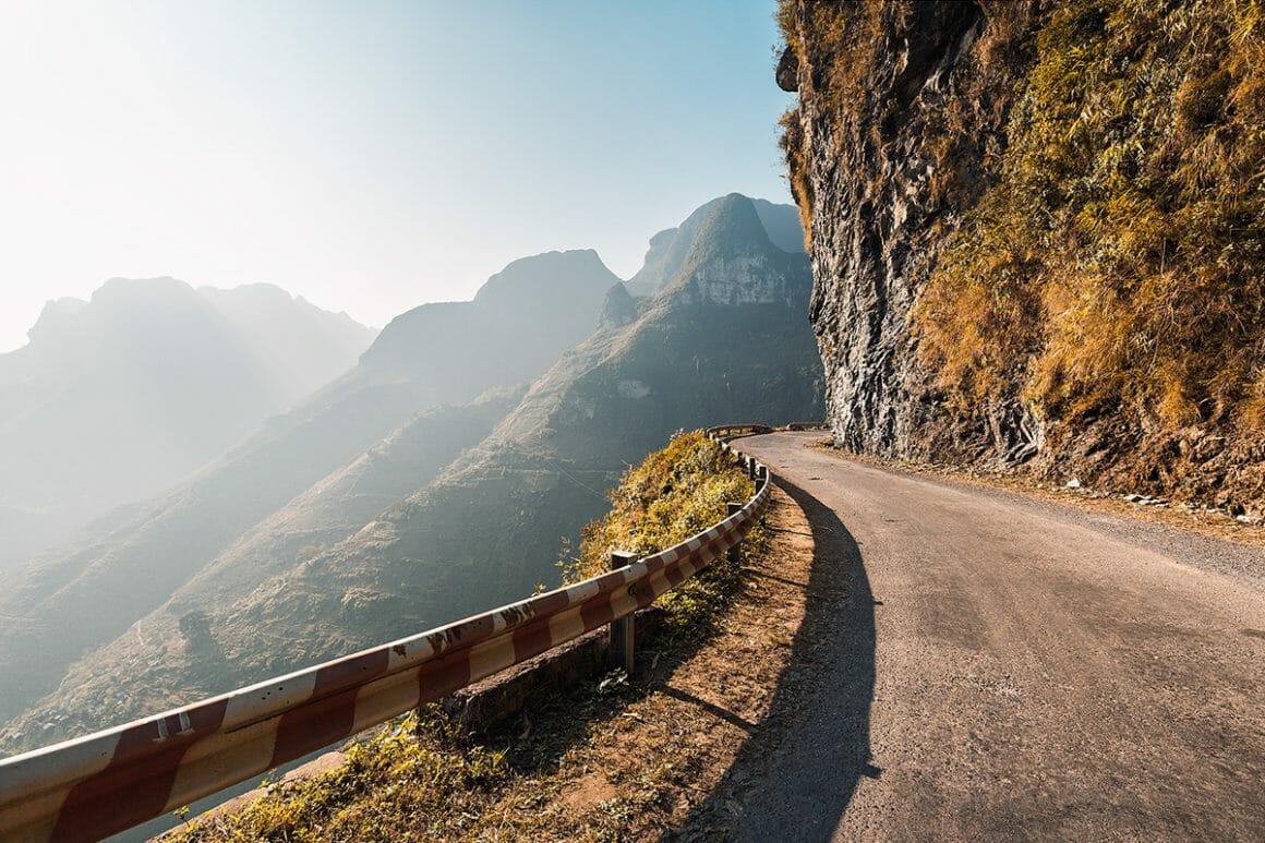 Voici une des impressionnantes photographies de Lukas Furlan : Vue d'une grande route qui longe le tour d'une montagne, éclairée également par les rayons du soleil.