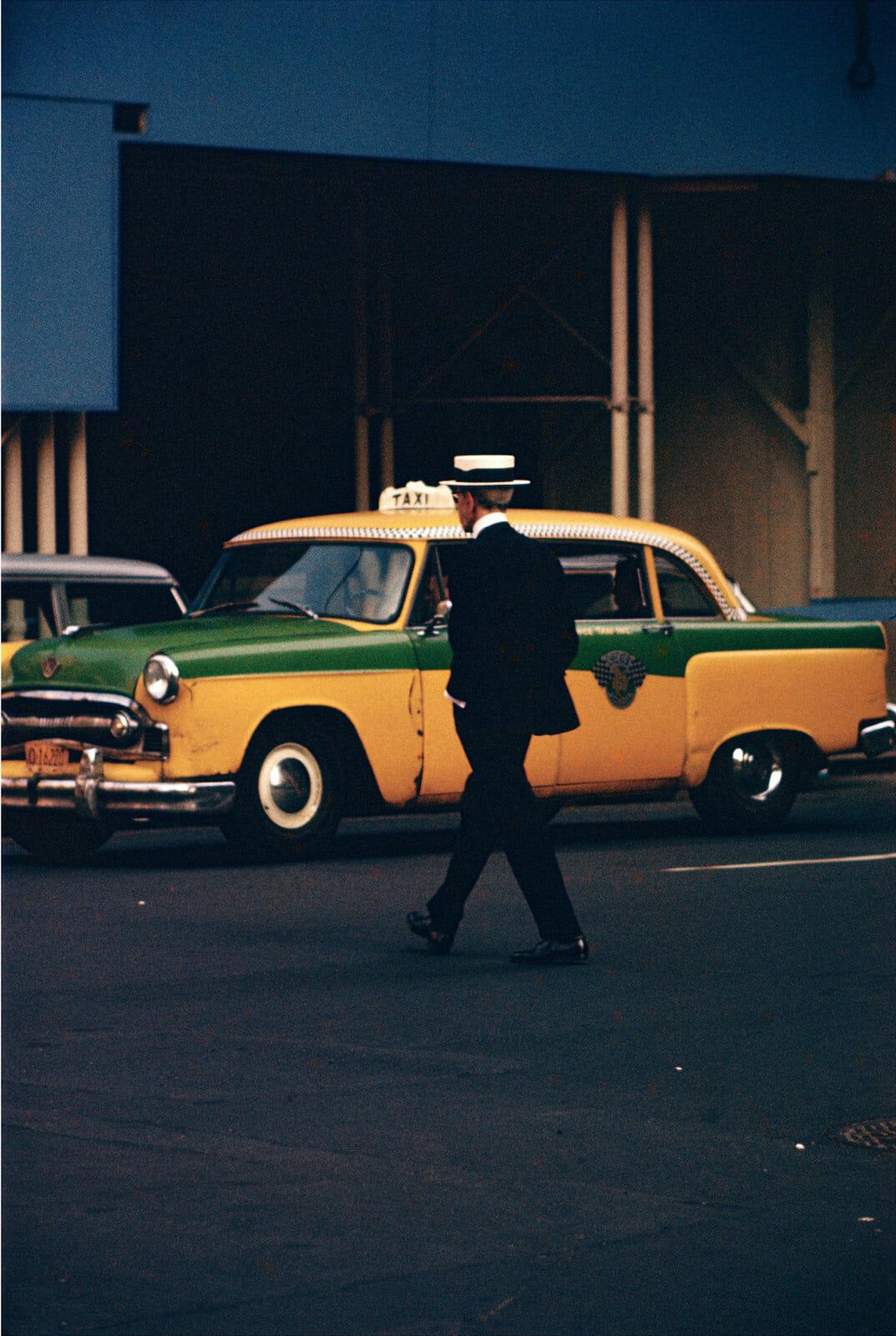 Photographie Saul Leiter, homme traversant devant un taxi