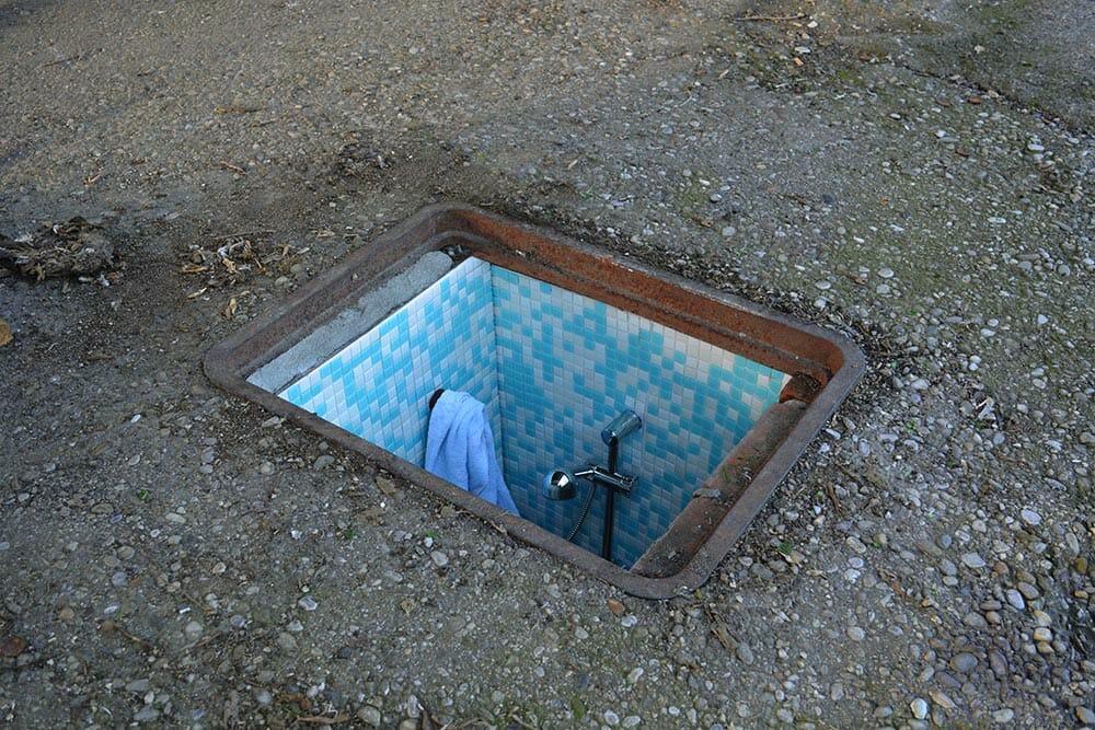 Issu de la série Borderline par Biancoshock, une bouche d'égout aménagée en douche.