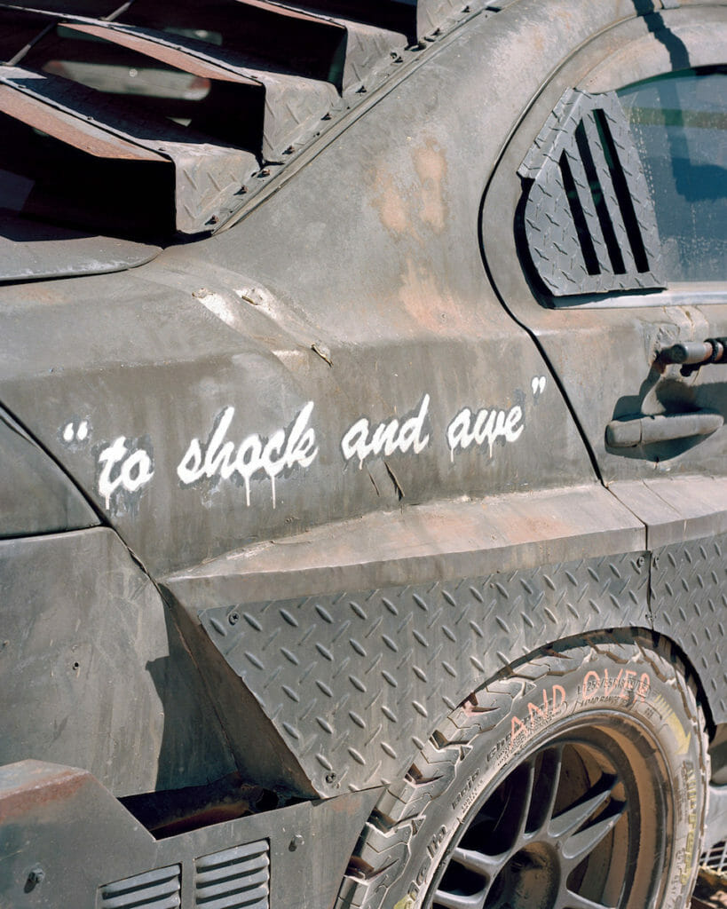 """Joe Pettet-Smith, Anarchy Tamed, gros plan sur l'inscription sur une voiture : """"to shock and awe""""."""