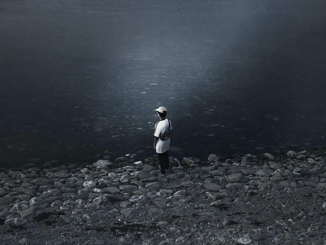 Kristoffer Axén, un personnage sur la plage regardant au loin.