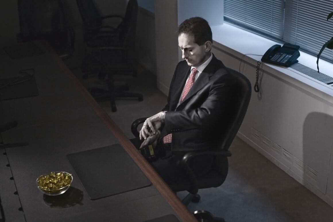Kristoffer Axén, un personnage qui regarde sa montre, installé à son bureau.