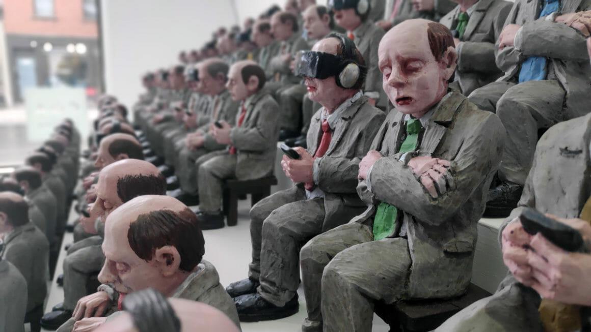 Isaac Cordal, détail de l'assemblée assises de petits personnages. Un des personnages a un casque de réalité virtuelle.
