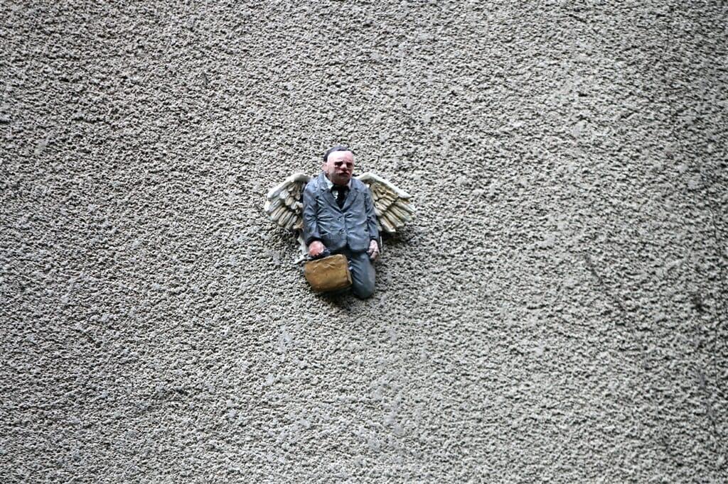 Isaac Cordal, une home miniature portant des ailes semblent sortir du béton.