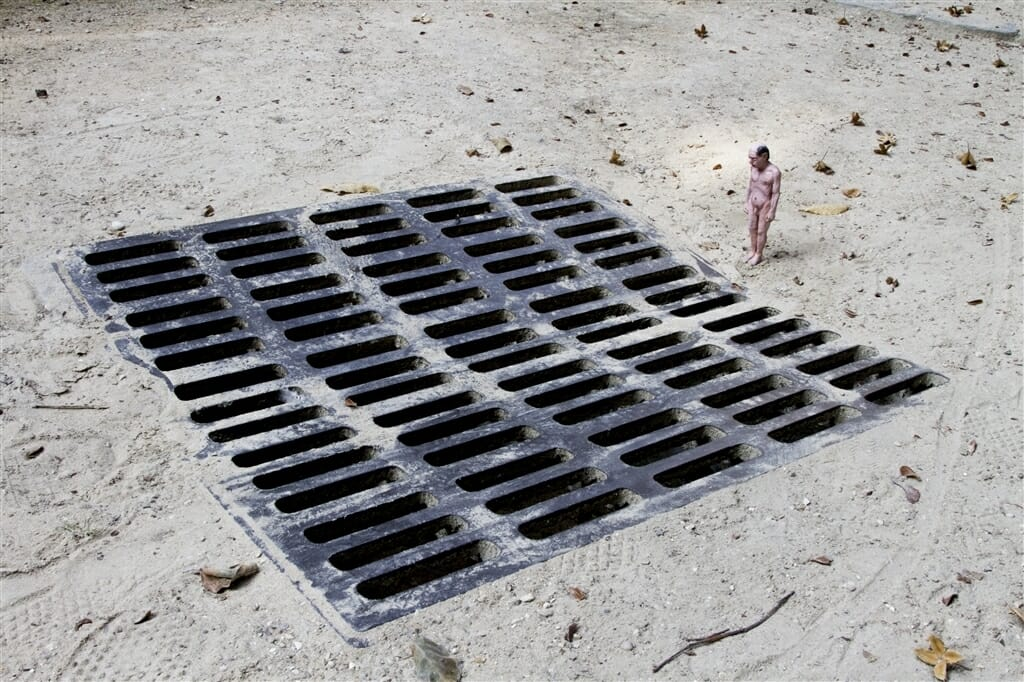 Isaac Cordal, un homme miniature nu qui regarde dans une bouche d'égout.