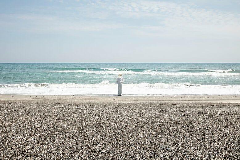 Yoshiki Hase photographie un homme sur une plage en combinaison blanche.