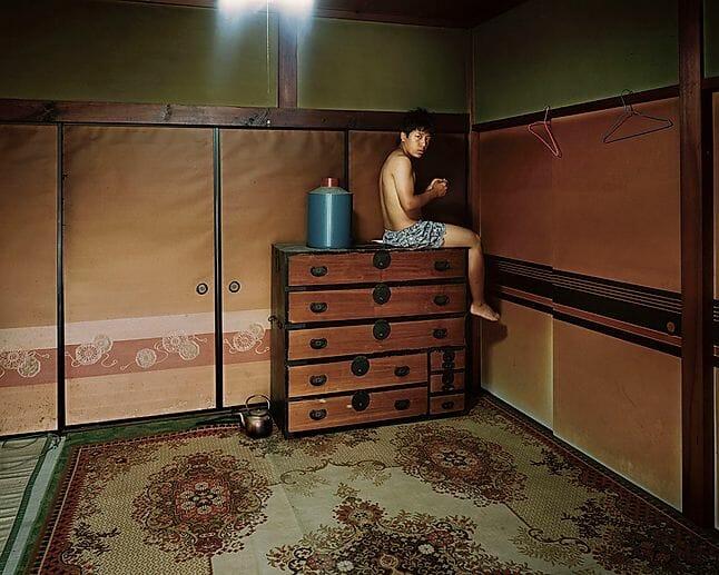 Yoshiki Hase, un homme sur une commode dans un intérieur japonais.