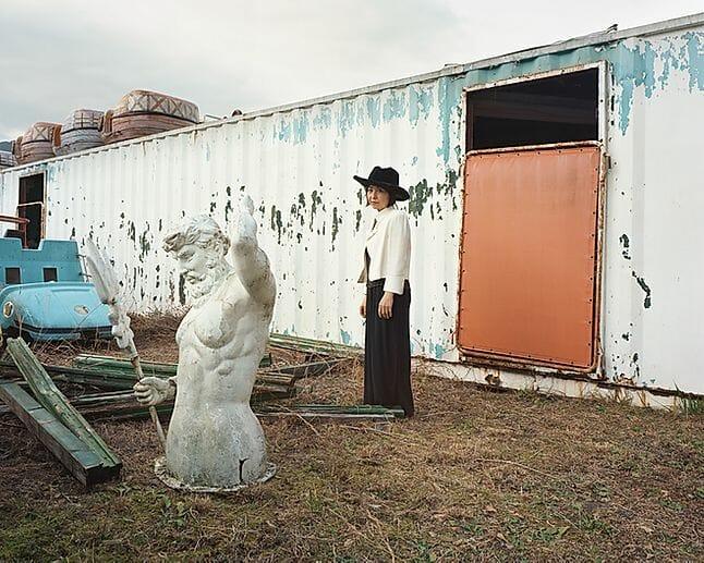 Yoshiki Hase, une femme à chapeau devant un conteneur.