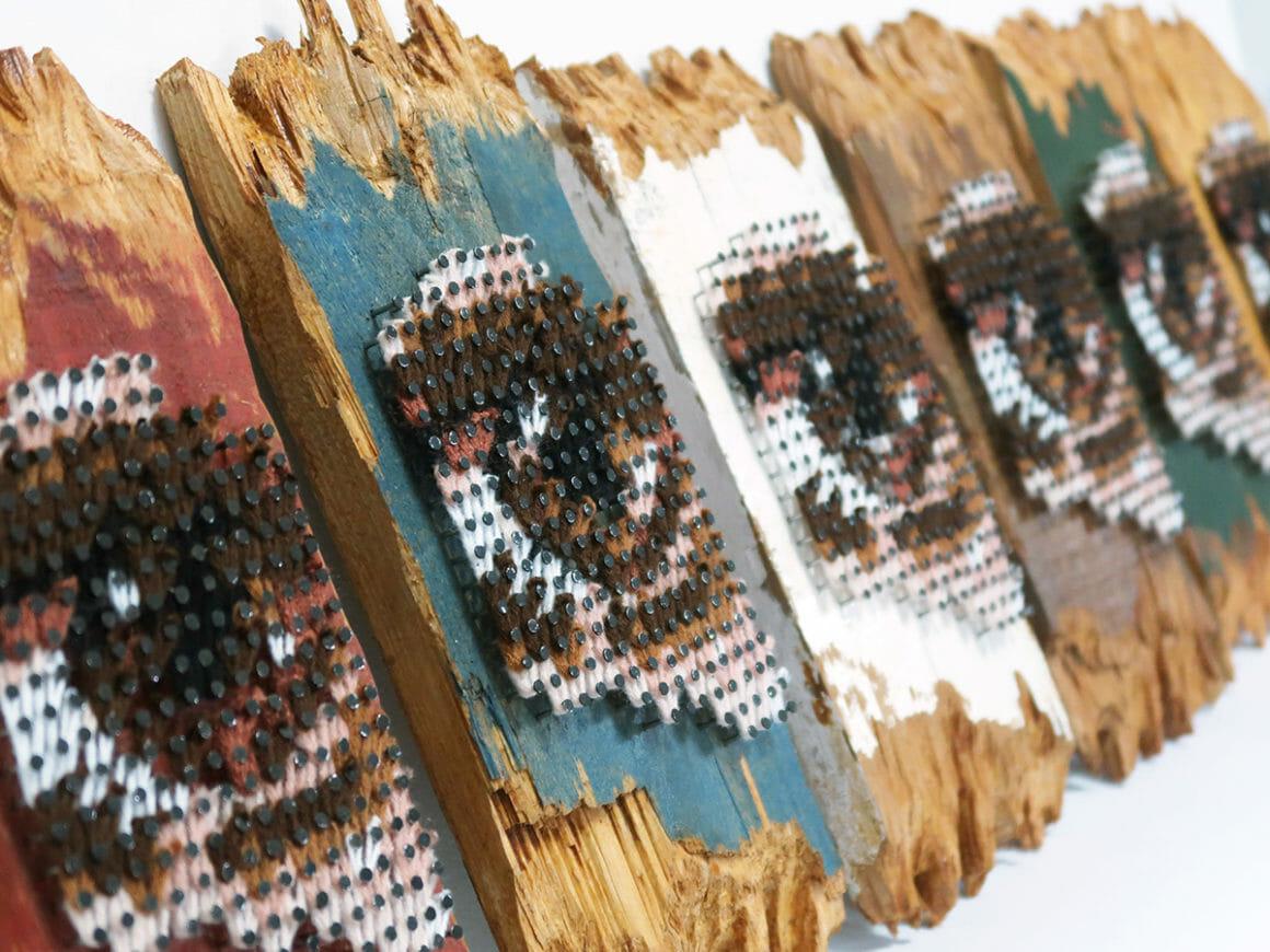 Aheneah, focus et vue de biais sur des panneaux de bois avec des yeux brodés.