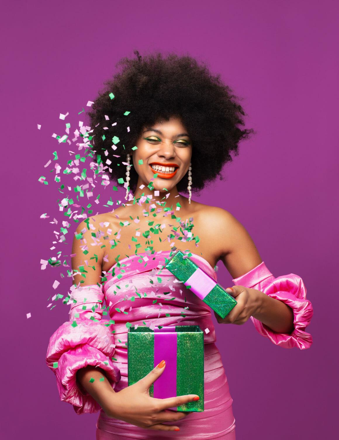 Une femme qui ouvre un cadeau d'où s'échappent des confettis.