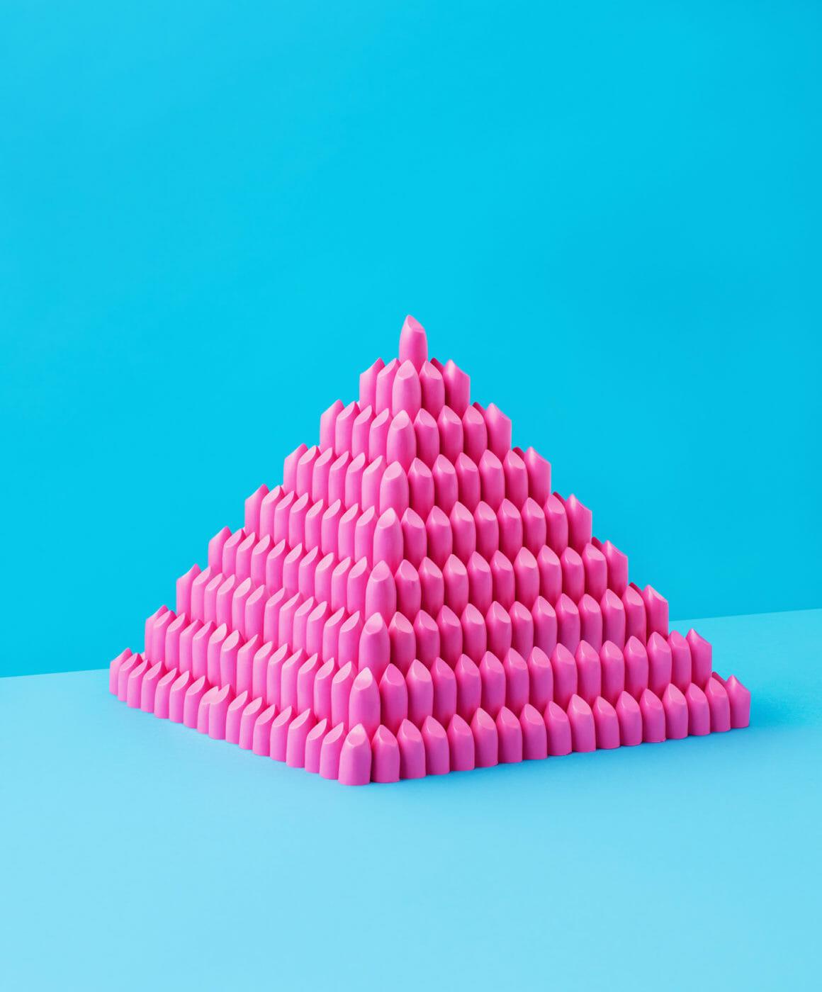 Une pyramide de rouge à lèvre rose sur fond bleu.