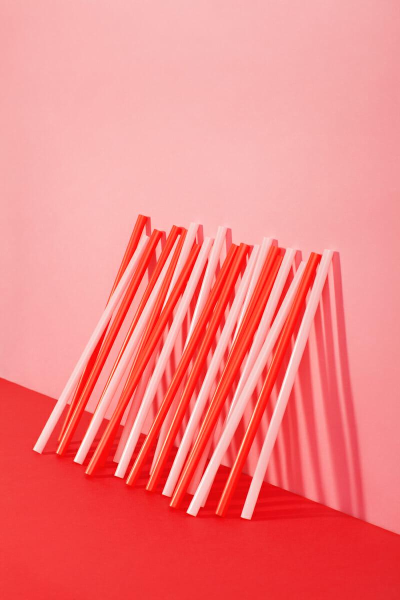 Une rangée de pailles posées contre un mur rose.