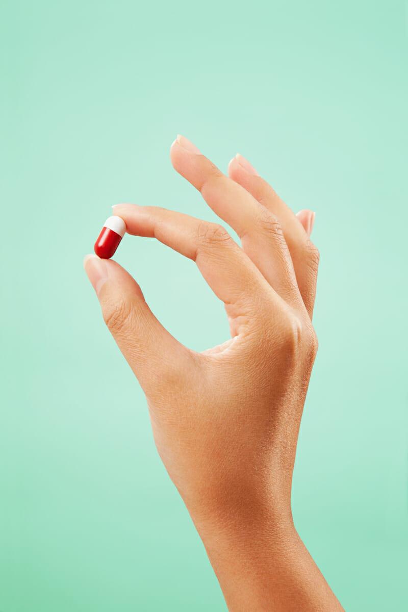 Une main sur fond bleu tenant une pilule rouge et blanche.