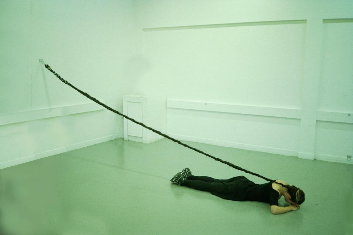 Reine Louve allongée sur le sol, une longue tresse accrochée au mur, performance,