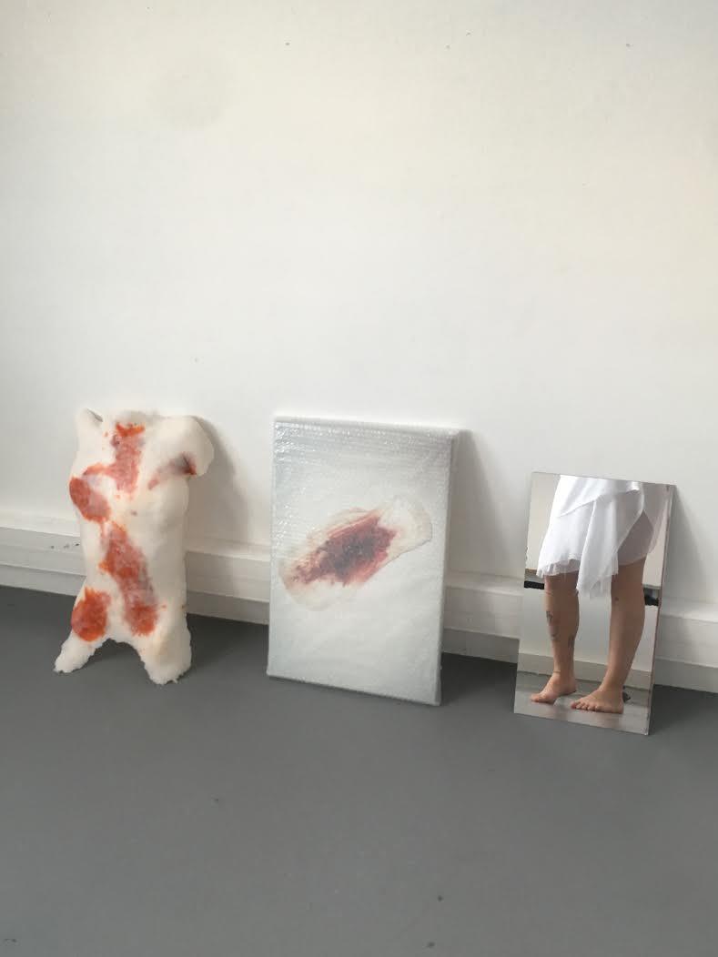 trois oeuvre, sculpture d'un corps, photo d'une serviette hygiénique, miroir