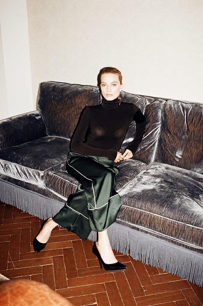margot robbie assise canapé gris argenté col roulé noir jupe longue verte photo Peter Kaaden