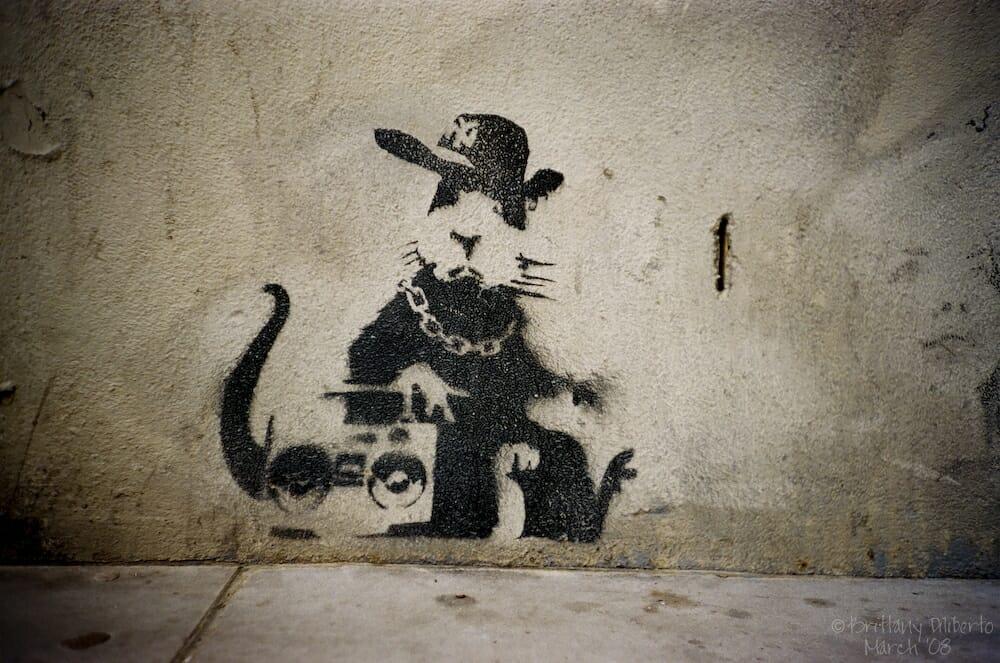 Un rat au pochoir sur un mur avec un ghetto blaster