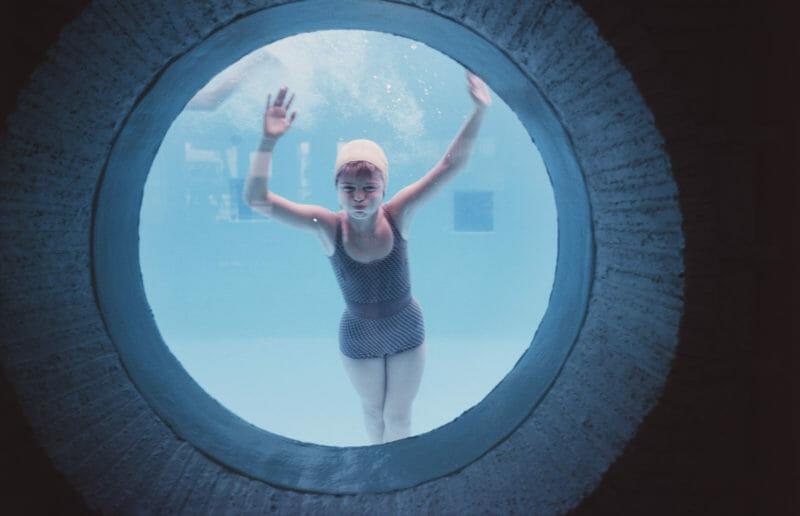 femme se baigne dans piscine hublot bonnet bain blanc