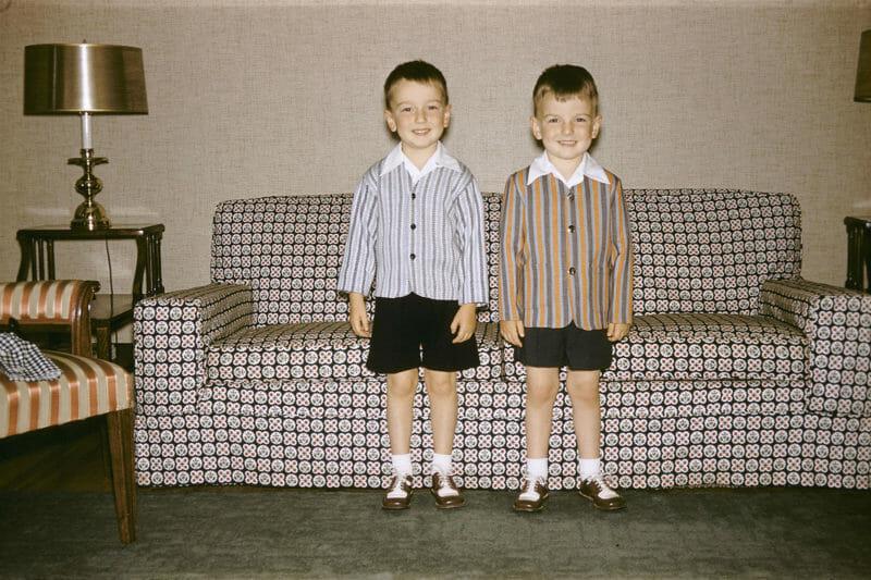 canapé motifs jumeaux garçons debout chemises short noirs chaussettes blanches