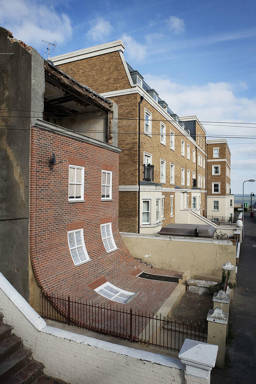 """L'artiste Alex Chinneck a réalisé """"From the knees of my nose to the belly of my toes"""", une façade de maison qui semble avoir glissée"""