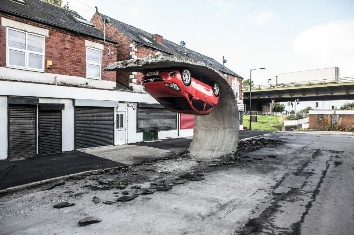 """""""Pick yourself up and pull yourself together"""" est une oeuvre d'Alex Chinneck représentant une voiture accrochée à l'envers sur une vague de goudron arrachée du sol"""