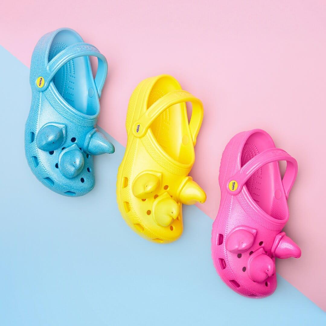 Photographie de trois crocs, jaune, rose et bleu sur fond rose et bleu pastel