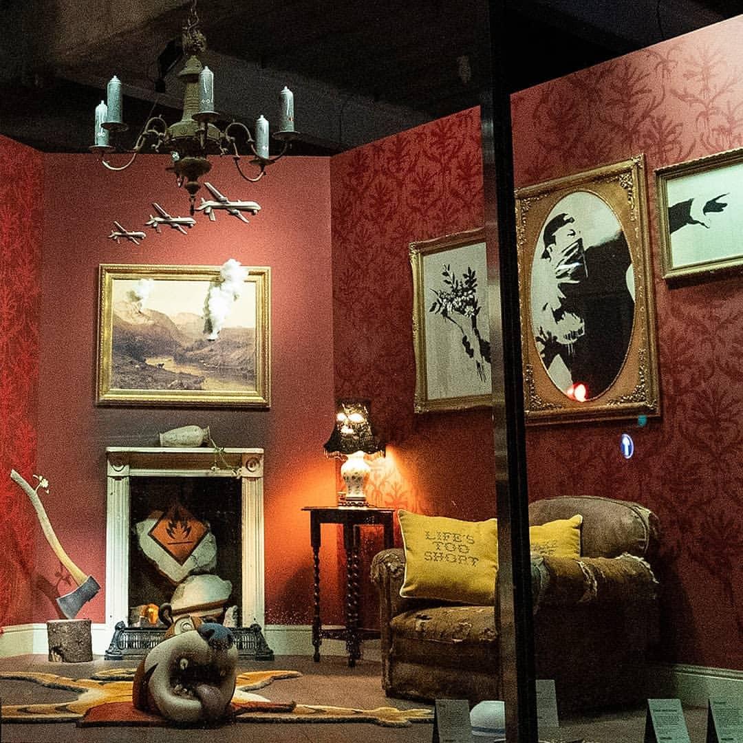 Photo de la boutique éphémère de Banksy, des tableaux, un fauteuil abimé et divers ojets