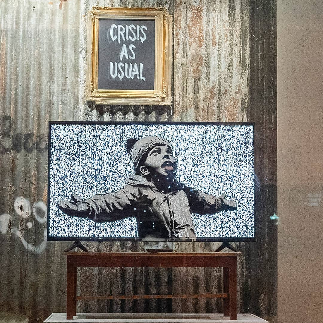 """Boutique éphémère de Banksy, un écran affiche un pochoir d'un enfant et un tableau affiche le slogan """"crisis as usual"""""""