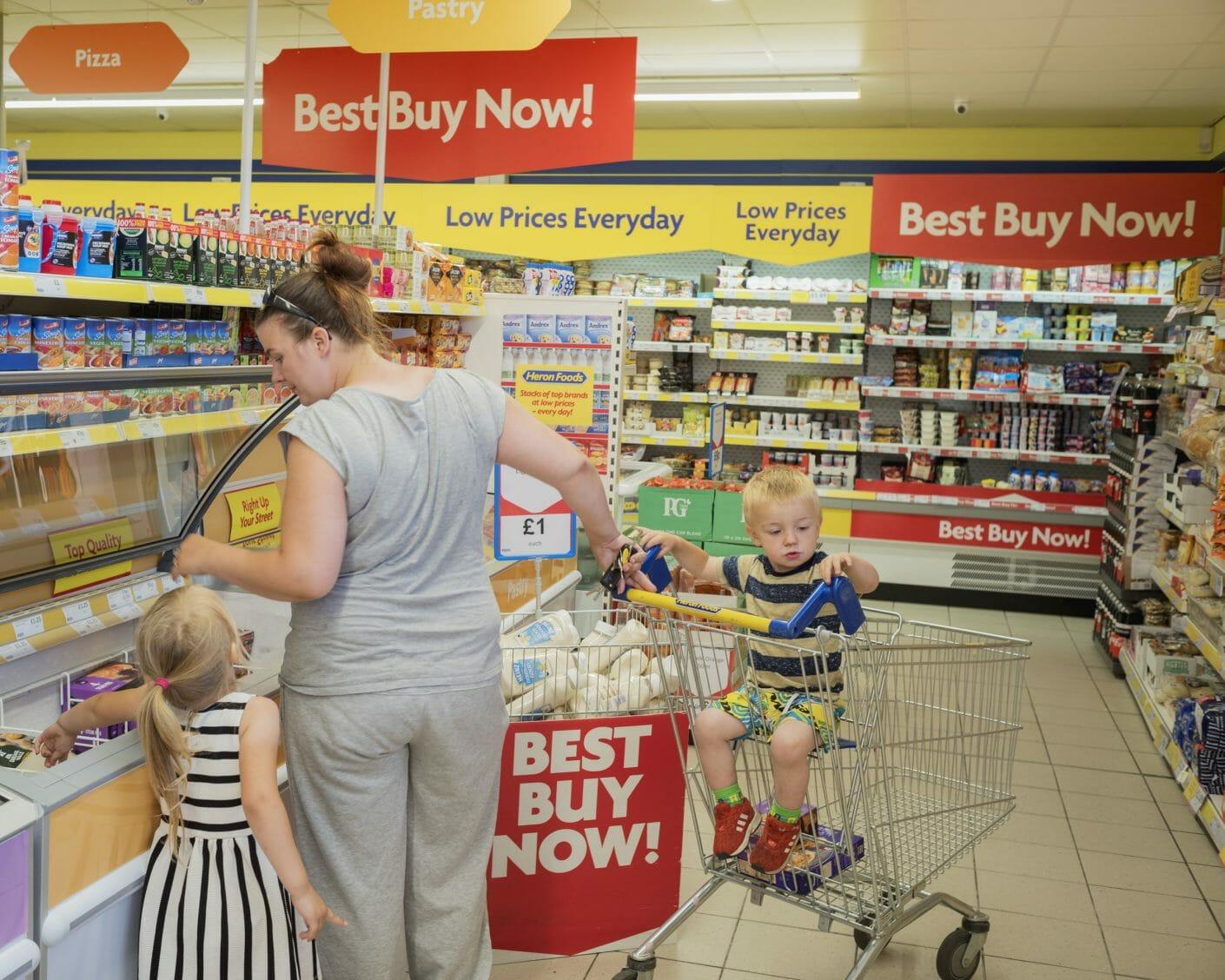 """Une mère et ses deux enfants font les courses, de nombreux panneaux """"best buy now"""""""
