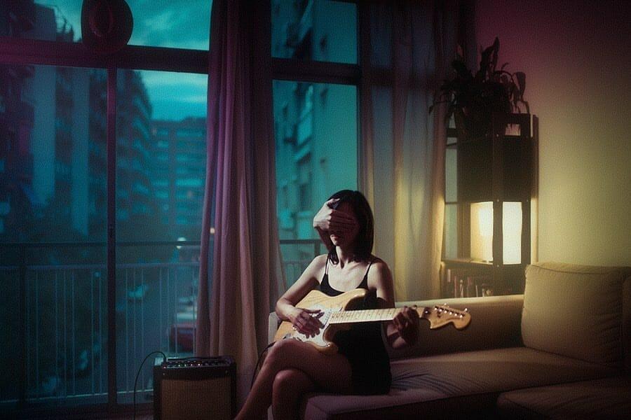 Une femme assise sur un canapé joue de la guitare. Une main sortie de nulle part lui cache le visage