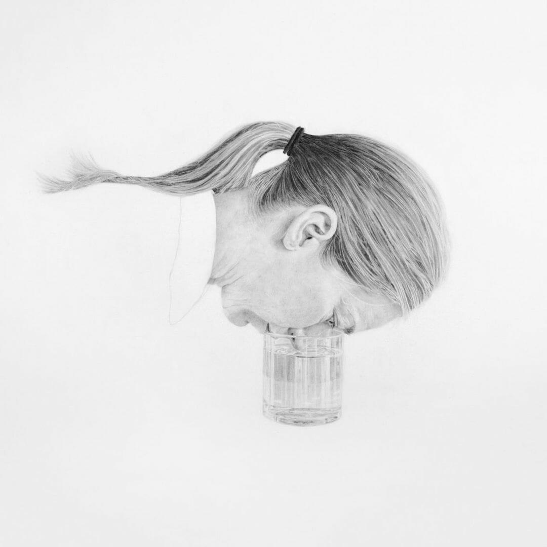 Une femme a la tête penchée et son net rentre dans un verre d'eau et frôle la surface du liquide qui est dedans