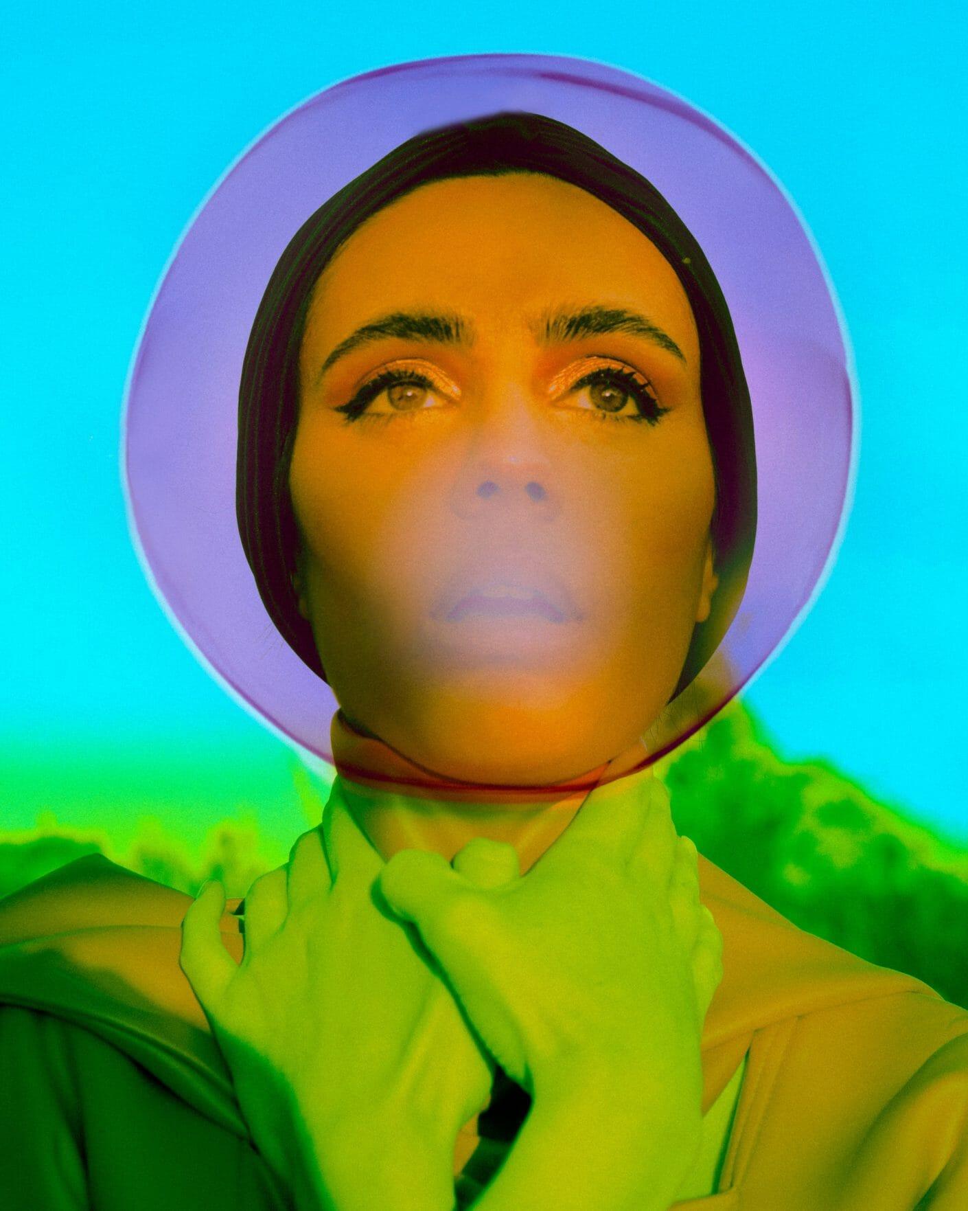 Portrait d'une femme, halo de violet autour de son visage. Ses mains autour de son cou sont vertes