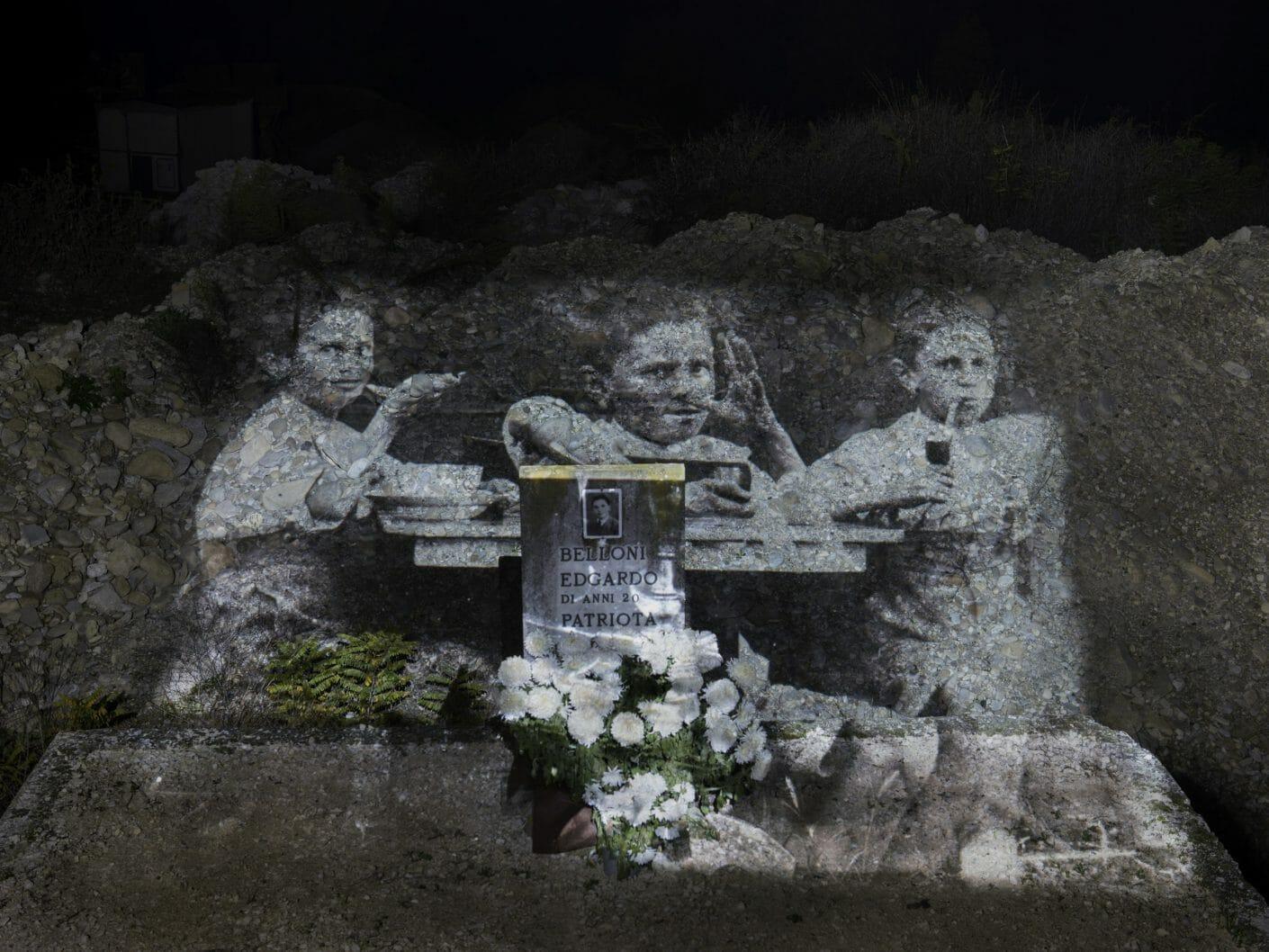 Mur de pierre et tombe sur laquelle est projetée une photographie d'enfants