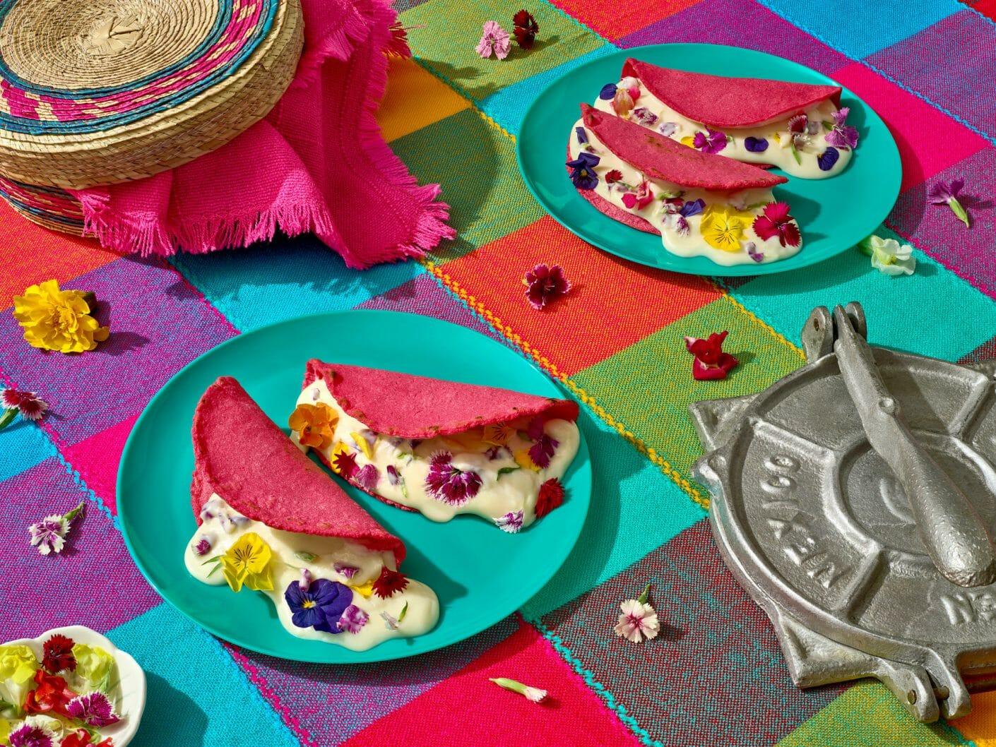 Assiettes de tacos roses dont sort une crème remplie de lfeurs