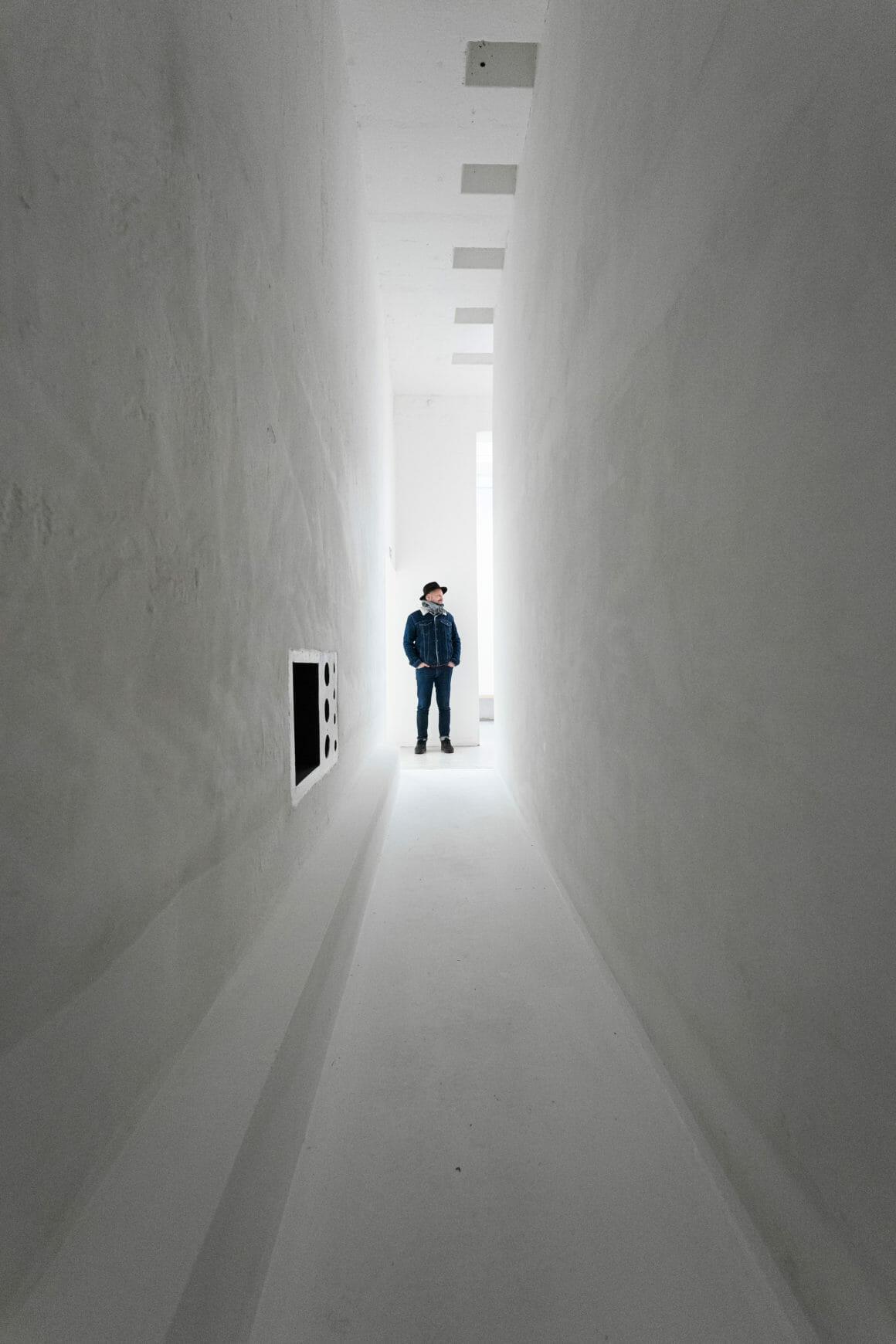 Photo d'un long couloir aux murs blancs au bout duquel il y a un homme