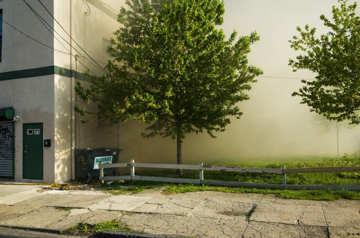 Premier plan d'un rue avec en arrière plan de la fumée