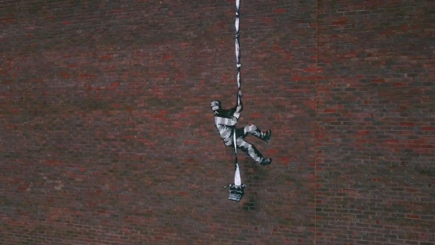 Create Escape, pochoir sur mur de Banksy, un prisonnier qui s'échappe à l'aide du papier d'une machine à écrire