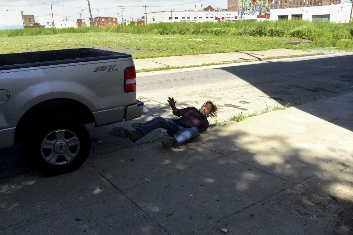 Homme à terre derrière une voiture