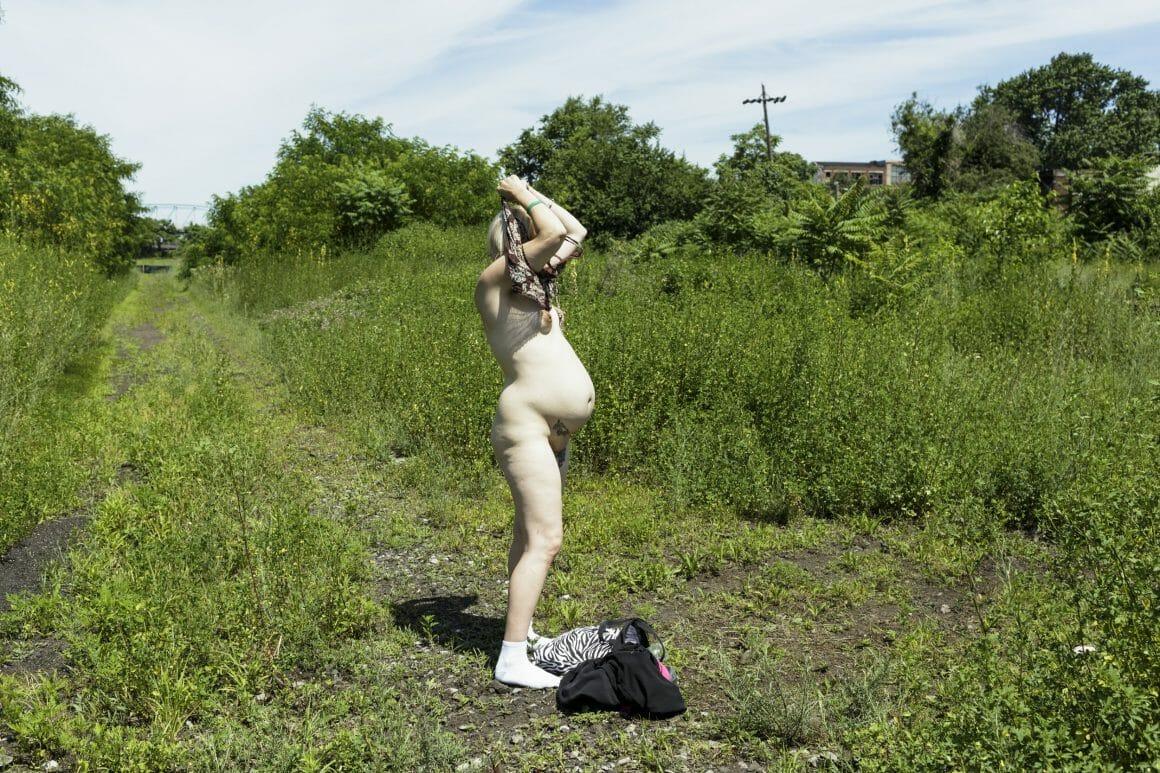 Femme enceinte nue se rhabillant