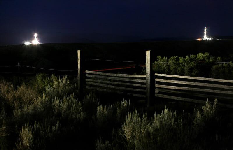 Une clôture dans la nuit. Végétation très présente. Au loin, deux forages dont de la lumière dans cette atmosphère sombre.