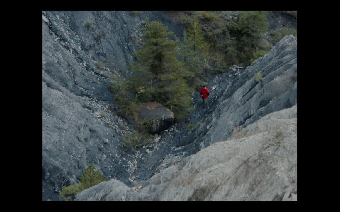 Vue de haut d'une personne en train de marcher entre les montagnes