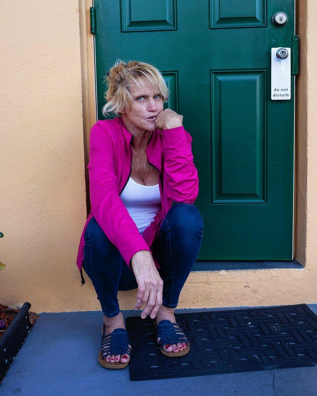 Une femme âgée est assise sur le perron d'une maison. Elle porte un gilet rose flash.