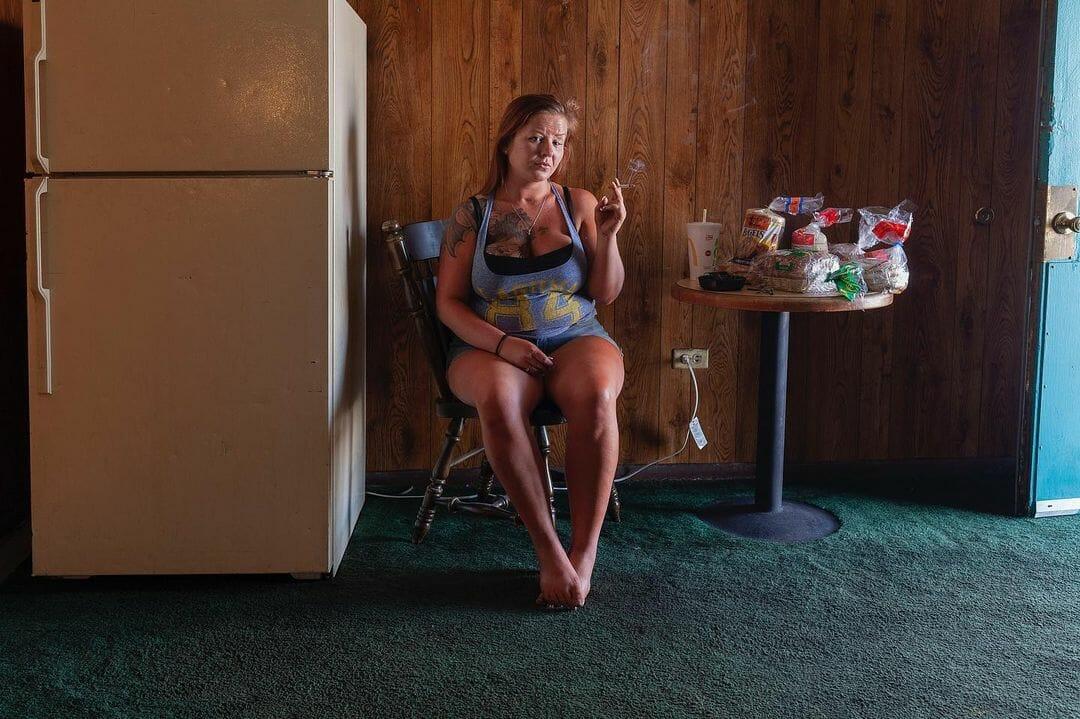 Une femme assise sur une chaise entre un frigo et une table sur laquelle il y a des paquets de pain de mie. Elle fume une cigarette.